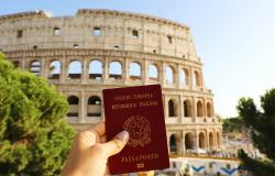 Hand holding Italian passport in front of Colosseum in Rome