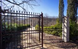 Paved driveway and wrought iron gates leading to property