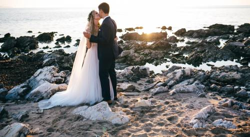 Bride and groom kissing near the sea