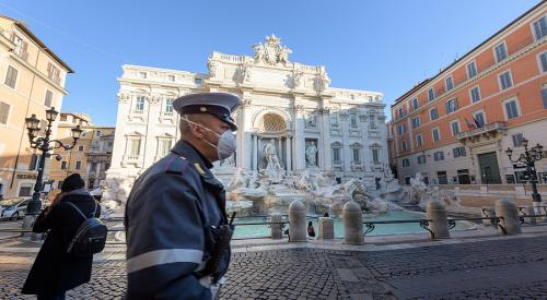 Policeman with face mask in front of Trevi fountain in Rome