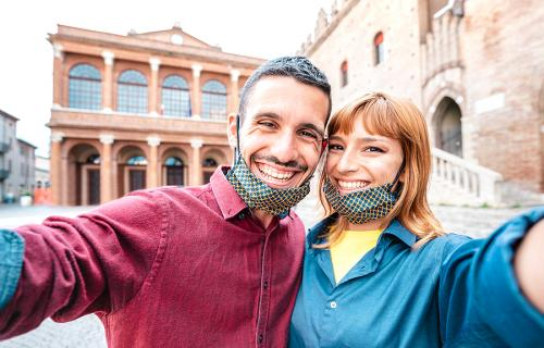 Smiling couple wearing face masks in Italy