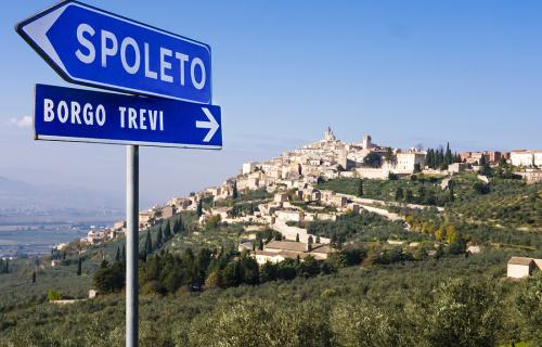 Road signs in Umbria with village in the background