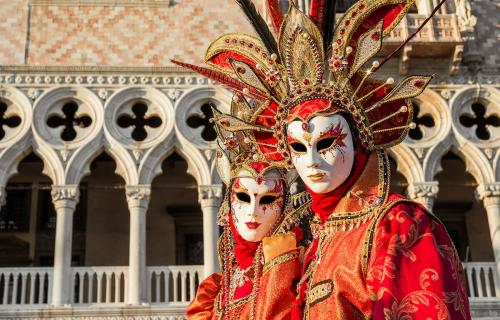 Two beautiful venetian carnival masks with the famous Doge Palace in the background