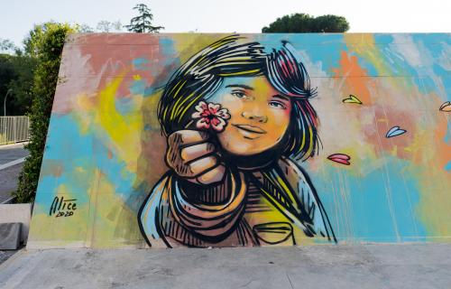 Wall painted by the artist with a little girl who give a flower