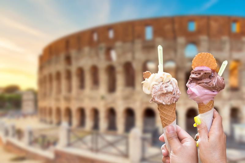 Hands holding gelato cones in front of Colosseum in Rome Italy